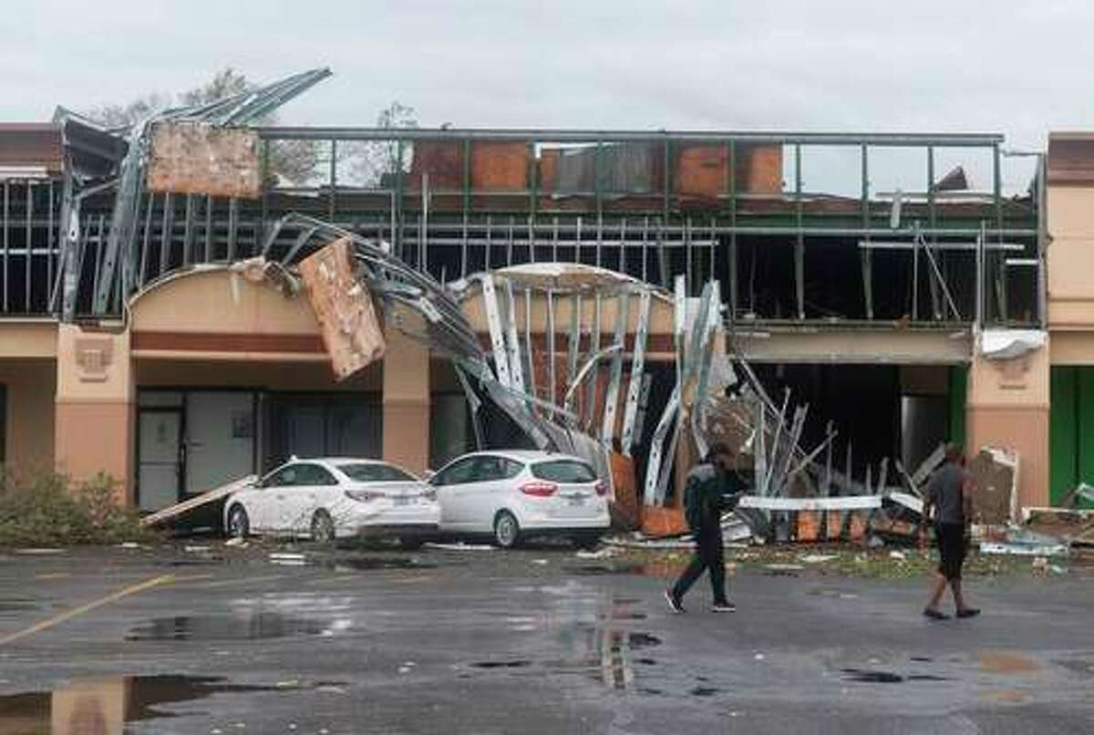 People walk past a destroyed building after the passing of Hurricane Laura in Lake Charles, Louisiana on August 27, 2020. - Hurricane Laura slammed into the southern US state of Louisiana Thursday and the monster category 4 storm prompted warnings of