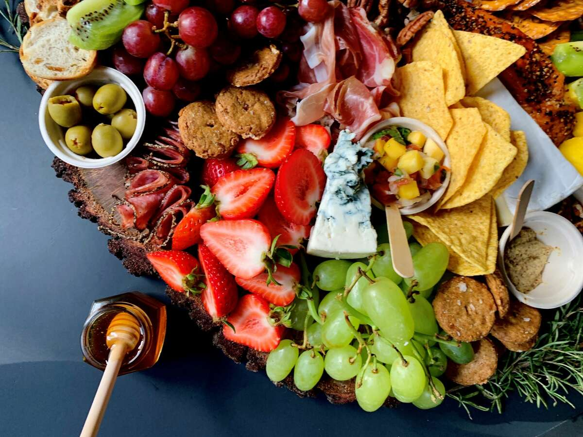 Charcuterie boards are often meticulously designed trays filled with crackers, meats, cheeses, jams, fruit and more that create a collage of snacks for small or larger groups to enjoy. It is often served with wine.