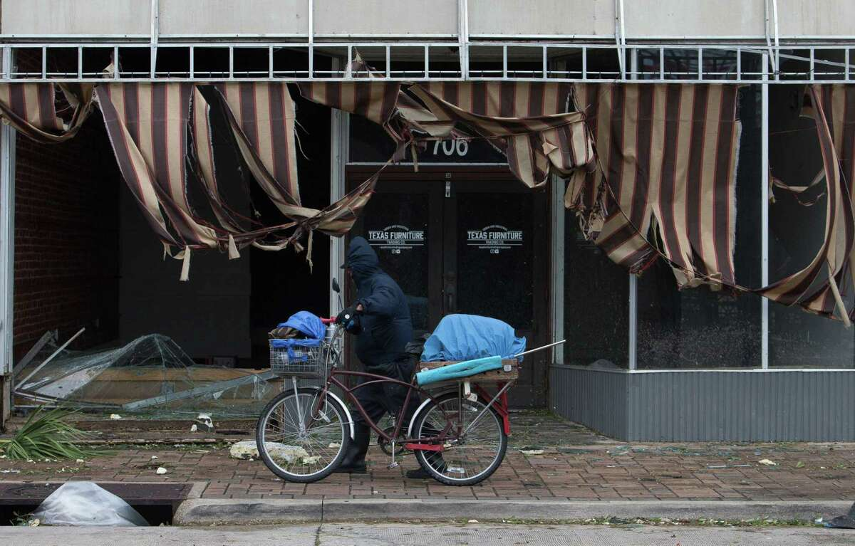 A man pushes his bicycle along a store damages during Hurricane Laura, Aug. 27, 2020, in Lake Charles, Louisiana.