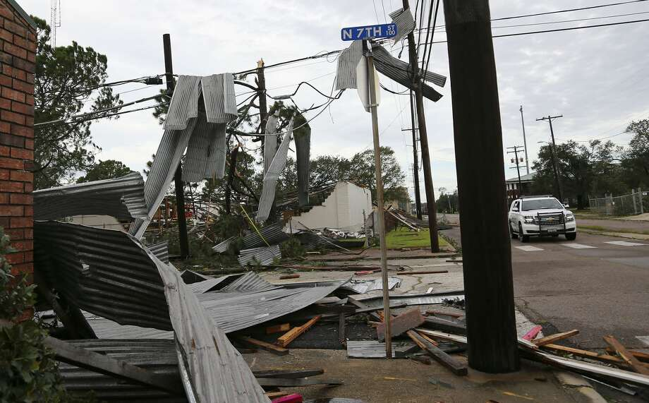 Sheet metal hangs off a building, trees and wires in downtown Orange, Texas after Hurricane Laura in Orange on Thursday, Aug. 27, 2020. Photo: Elizabeth Conley/Staff Photographer / © 2020 Houston Chronicle