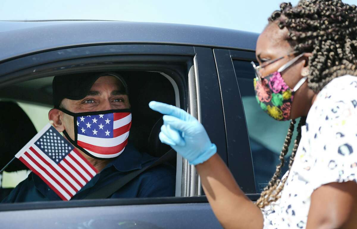 SANTA ANA, CALIFORNIA - JULY 29: Omar Abdalla, originally from Palestine, holds an American flag after being sworn in as a new U.S. citizen by an immigration service officer (R) from his vehicle at a drive-in naturalization ceremony amid the COVID-19 pandemic on July 29, 2020 in Santa Ana, California. The naturalization ceremony welcomed around 268 immigrants who took the citizenship oath and pledged allegiance to the American flag as the spread of the coronavirus continues. U.S. Citizenship and Immigration Services temporarily suspended in-person ceremonies for nearly three months to help slow the spread of COVID-19. (Photo by Mario Tama/Getty Images)