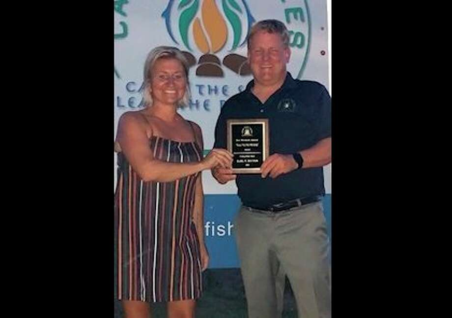 Camp Fish Tales Executive Director Shannon Forshee presents the Keeper of the Fire award to Board Member Karl Ieuter. (Photo provided)