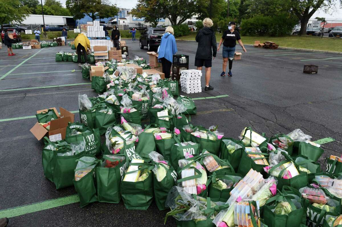 Volunteers and organizers help distribute groceries during a mass drive-through and walk-through food distribution event on Thursday morning, Aug. 27, 2020, on Broadway in Albany, N.Y. The event was hosted by Catholic Charities of the Diocese of Albany and the Regional Food Bank of Northeastern New York and local community partners. The groups say they have served an estimated 50,000 people, providing them with over 500 tons of fresh, frozen and shelf-stable food items. (Will Waldron/Times Union)