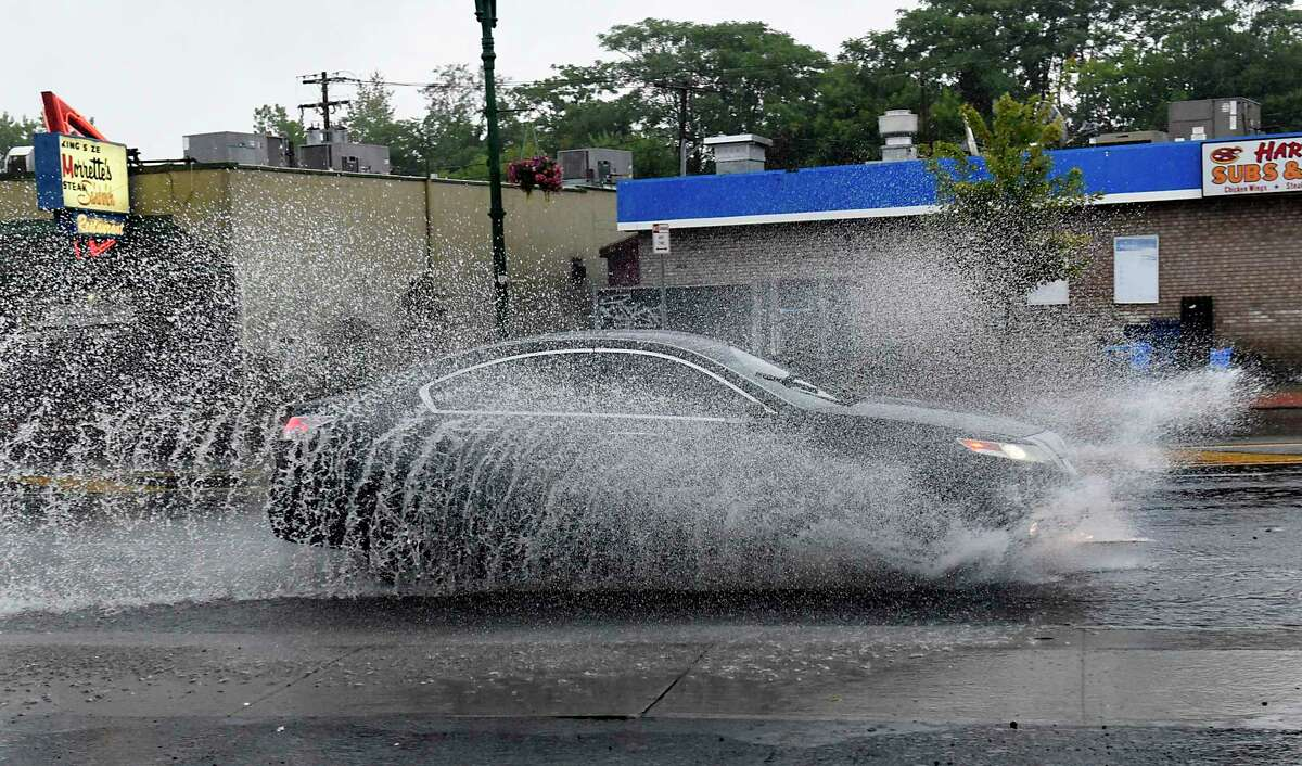 A car drives through a partially flooded Erie Blvd. during a downpour on Thursday, Aug. 27, 2020 in Schenectady, N.Y.(Lori Van Buren/Times Union)