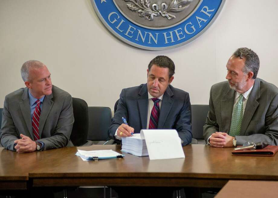 Texas Comptroller Glenn Hegar, center, certifies the 2020-21 state budget as Associate Deputy Comptroller for Fiscal Matters Phillip Ashley, left, and Director of Fiscal Management Rob Coleman, right, look on in this file photo from 2019. Photo: Courtesy Photo