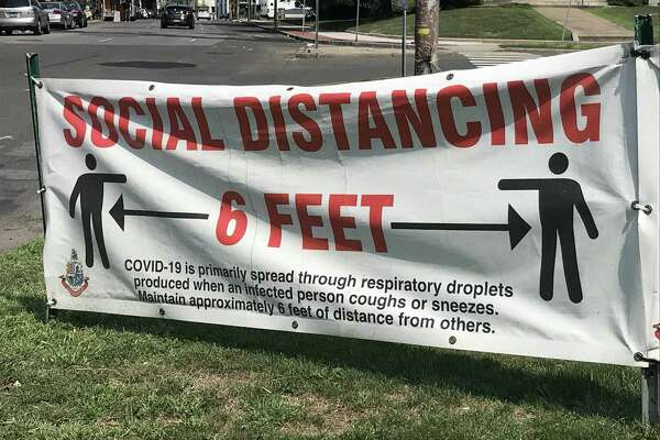 A sign advising residents to maintain 6 feet of distance, seen in Stamford.