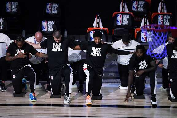 Los Angeles Clippers players kneel in honor of the Black Lives Matter movement during the playing of the national anthem prior to an NBA basketball game against the Dallas Mavericks Thursday, Aug. 6, 2020 in Lake Buena Vista, Fla. (AP Photo/Ashley Landis, Pool)