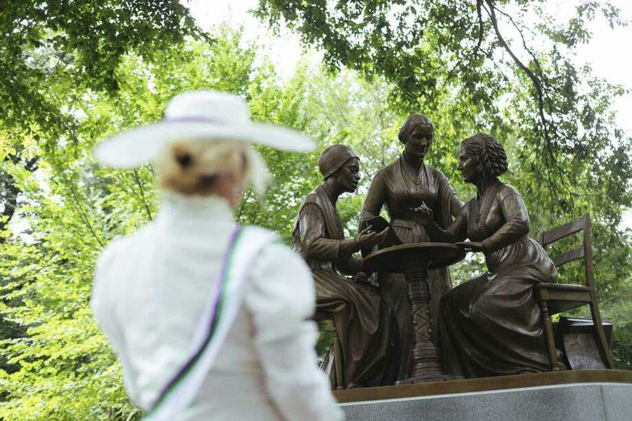 Mona Cahill, costumed as a women suffrage activist, stood in front of the Women's Rights Pioneers statue in Central Park Wednesday, Aug. 26, 2020, in New York. The statue, created by Ridgefield sculptor Meredith Bergmann and featuring Sojourner Truth, Susan B. Anthony and Elizabeth Cady Stanton, is the first monument in the park honoring any female historical figures. Photo: Photo: Kevin Hagen / AP