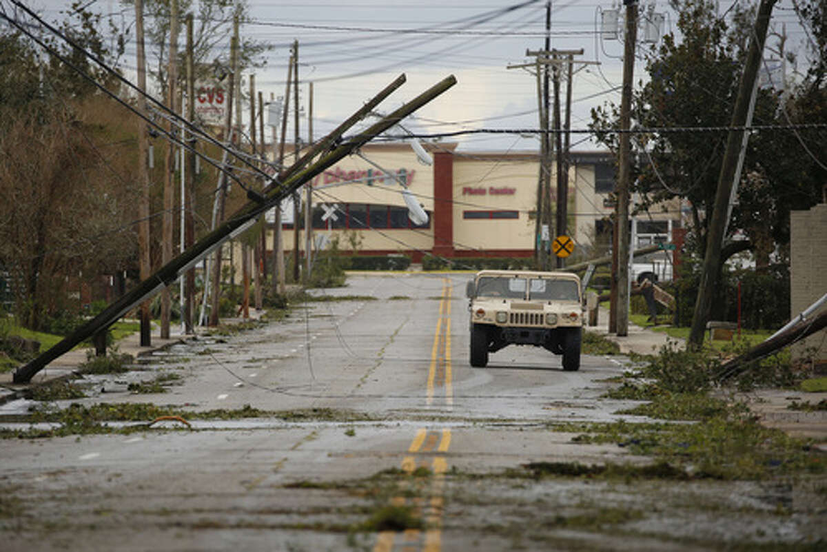 """A Louisiana National Guard humble drives past utility poles damaged after Hurricane Laura made landfall in Lake Charles, Louisiana, U.S., on Thursday, Aug. 27, 2020. Hurricane Laura raked across Louisiana early on Thursday, becoming one of the most powerful storms ever to hit the state with a """"catastrophic storm surge,"""" flash floods and devastating winds that could inflict more than $15 billion in insured losses. Photographer: Luke Sharrett/Bloomberg"""