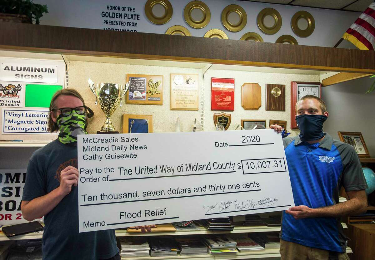 Aaron Hessling, left, and Tom Baker, right, of McCreadie Sales, hold up a check for $10,007 for United Way of Midland County's flood recovery efforts, proceeds from t-shirts and sweatshirts printed with an original design by cartoonist Cathy Guisewite, Thursday at McCreadie Sales in Midland. (Katy Kildee/kkildee@mdn.net)
