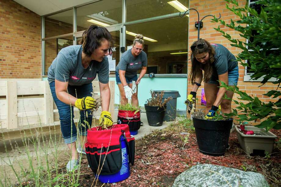 From left, Tara Holsinger, Mandy Walker and Alaina Bearss pull weeds near the entrance to Windover High School as they work as part of a group of volunteers from Dow to clear debris and plant landscaping at the school Thursday, Aug. 27, 2020. (Katy Kildee/kkildee@mdn.net)