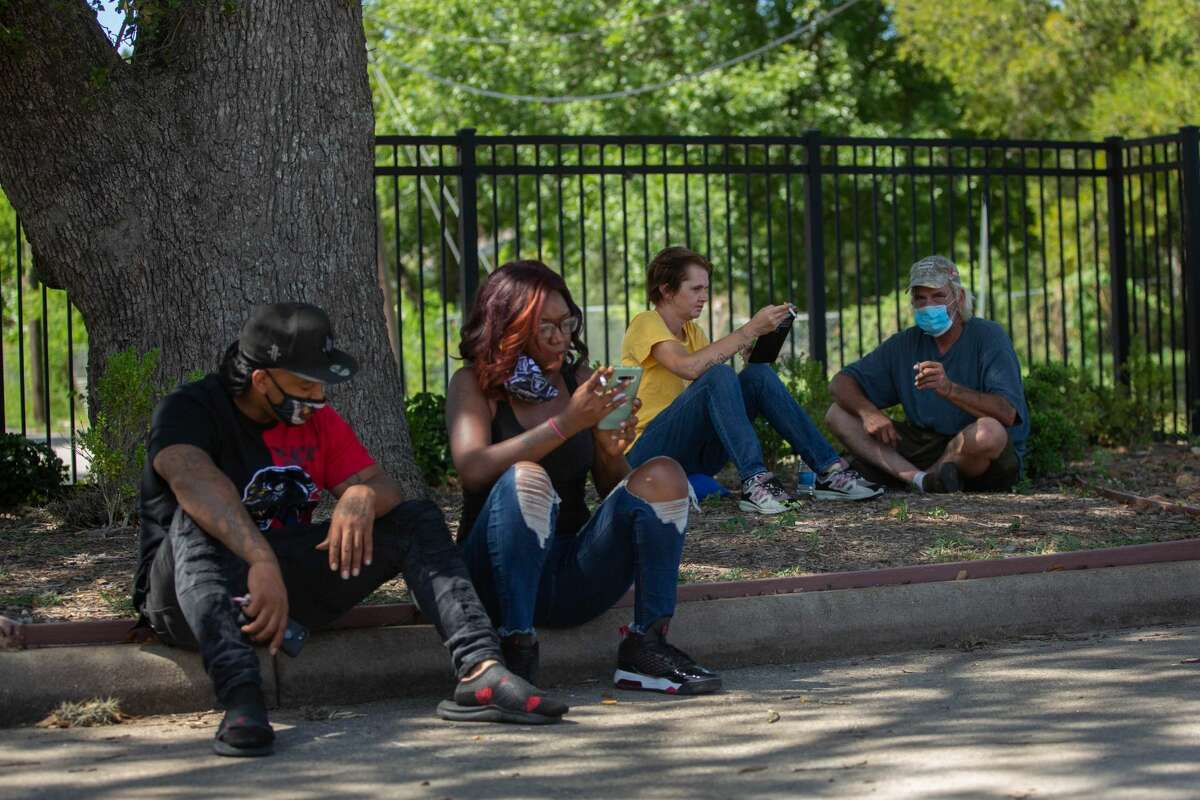 Refugess from Port Arthur and Beaumont take a smoke break outside of the Forge Red Cross station in Houston on August 27, 2020.