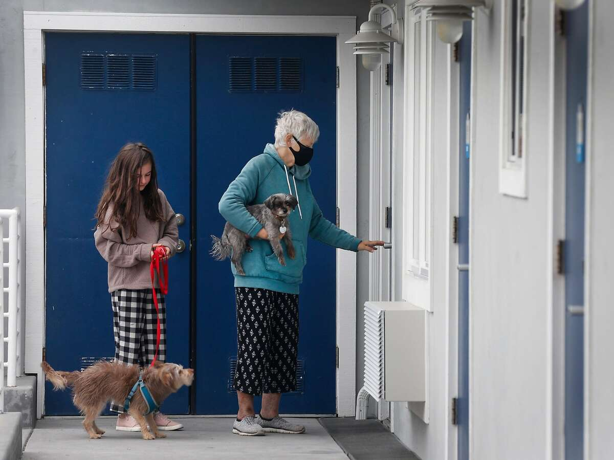 Marie Stefanesko and her granddaughter Lily Katznelson, 11, return to their hotel room at the Beach Street Inn and Suites while the family waits for evacuation orders to be lifted in Santa Cruz, Calif. on Thursday, Aug. 27, 2020. Hotels have experienced a spike in occupancies after welcoming local residents that have been temporarily displaced by wildfires.