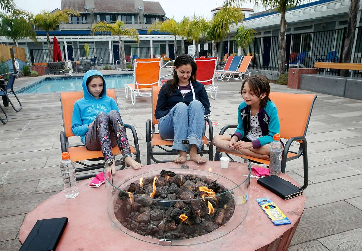 A family, evacuated from their home by the CZU Complex fire, read by the fire pit at the Beach Street Inn and Suites in Santa Cruz, Calif. on Thursday, Aug. 27, 2020. Hotels have experienced a spike in occupancies after welcoming local residents that have been temporarily displaced by wildfires.