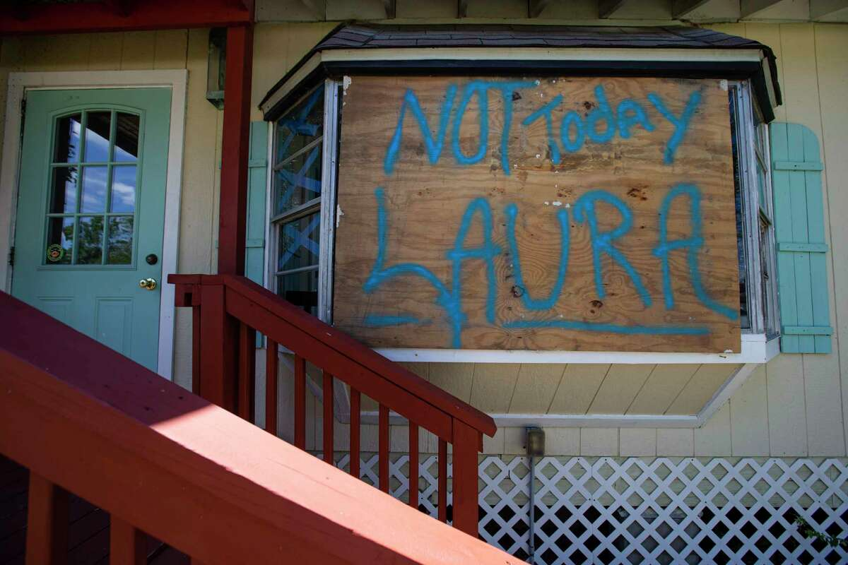 """A """"Not Today Laura"""" plywood sign remaines on The Clipper House Inn's cottage window after Hurricane Laura made landfall near Cameron, Louisiana Thursday, Aug. 27, 2020, in Kemah."""