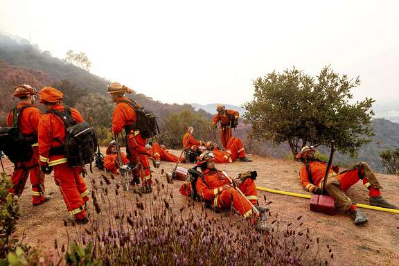 Inmate firefighters rest during a break from battling the River Fire in Salinas, Calif., Monday, Aug. 17, 2020. Fire crews across the region scrambled to contain dozens of blazes sparked by lightning strikes as a statewide heat wave continues. (AP Photo/Noah Berger)