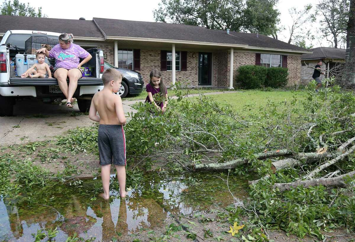 The Milligan family, Treysen, 1, from left, dog Khous, mom Meagan, Braxtyn, 9, Tyleigh, 7, and dad Tyler, work on the trees that fell around their Orange, Texas home because of Hurricane Laura on Thursday, Aug. 27, 2020. The family, that was flooded out of their home during Harvey decided to evacuate. They found a lot of fallen trees, but their home was untouched.
