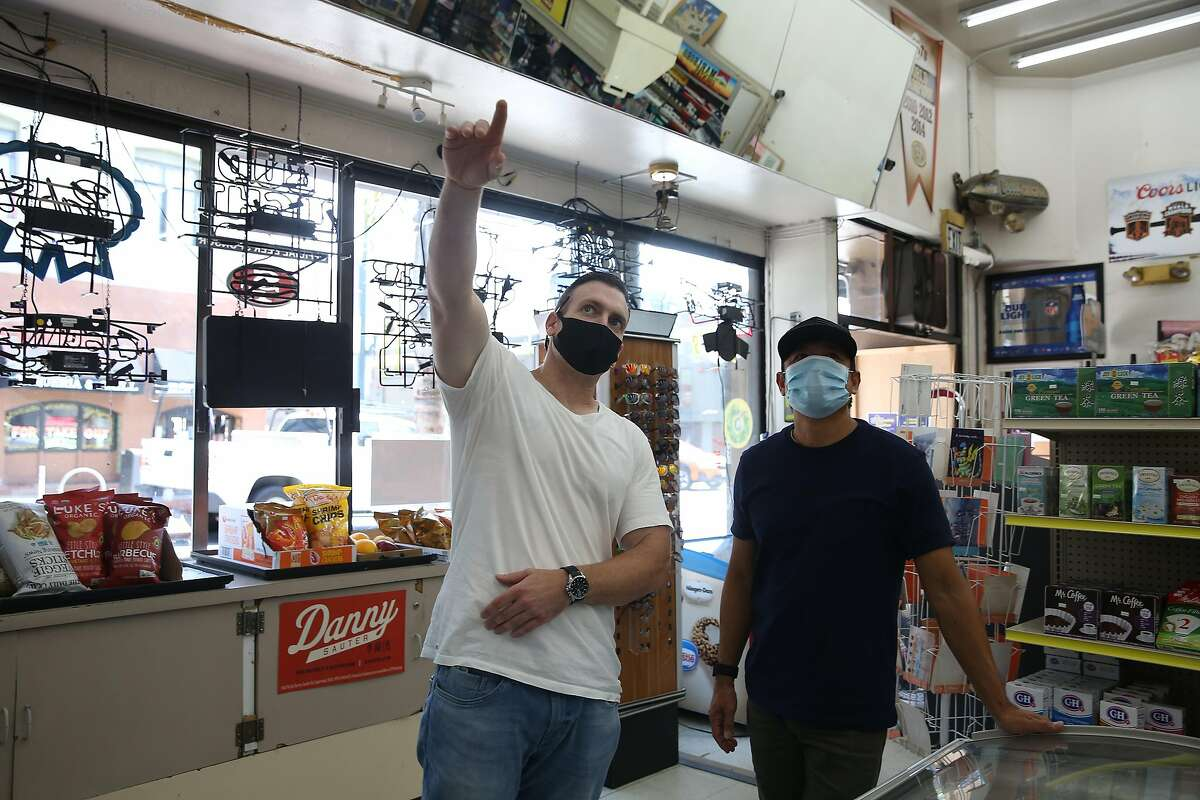 Jeffrey Choate (l to r) talks with Discount Grocers owner Warren Trinidad (left) who he was meeting with to talk about painting a mural in the store on Tuesday, August 18, 2020 in San Francisco, Calif.