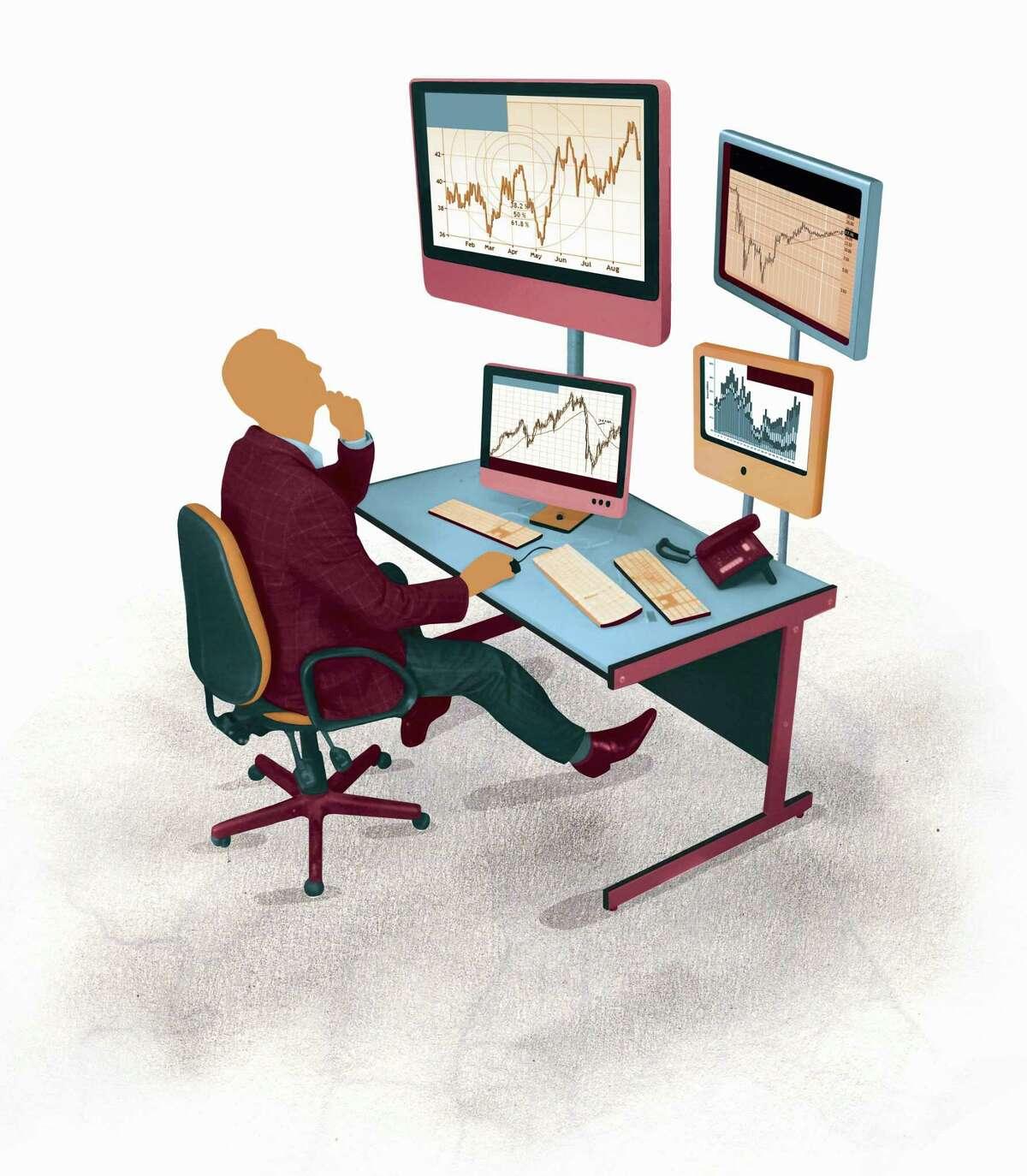 Businessman looking up at line graph charts on computer monitors