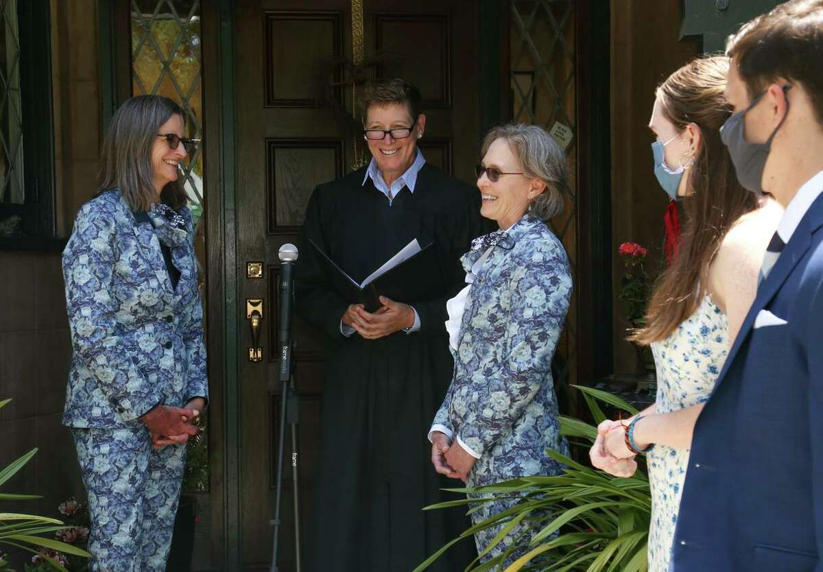 Anne Mitchell, left, and Joni Hauser are married by Judge Tara Flanagan in their Berkeley front yard on June 20with Hauser's children, Jeff Asa-Hauser and Kit Asa-Hauser.The couple were unmasked only during the ceremony, and a small group of guests maintained social distance.