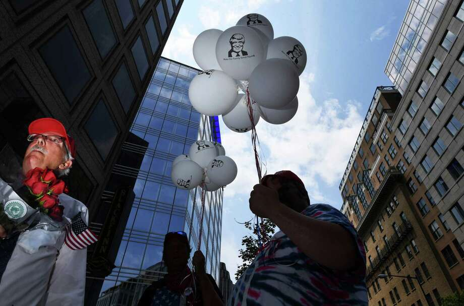 People carry balloons with President Trump's image on them following an event near the White House by the religious conservative group Public Advocate of the United States, hours before Trump was to accept the Republican nomination in a South Lawn speech. Photo: Washington Post Photo By Matt McClain / The Washington Post