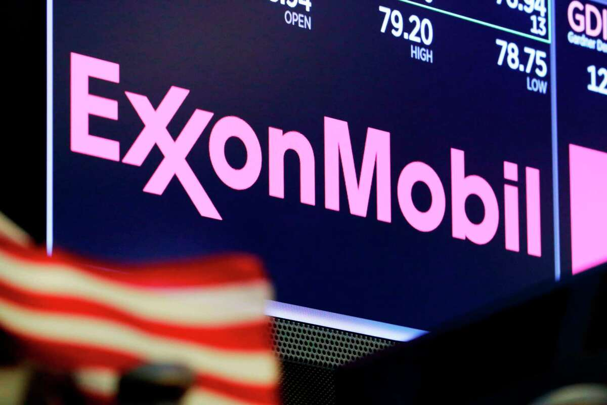 The logo for ExxonMobil appears above a trading post on the floor of the New York Stock Exchange. Exxon lost $1.1 billion in the second quarter, Friday, July 31, 2020, its economic pain deepening as the pandemic kept households on lockdown, diminishing the need for oil around the world.