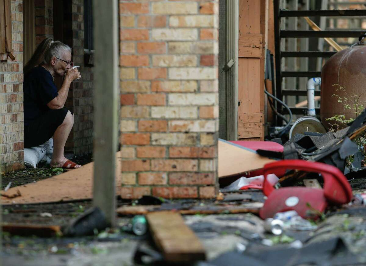 Linda Drounette, 78, drinks a cup of coffee while sitting on the frame of her front door, looking out to the debris left after Hurricane Laura on Thursday, Aug. 27, 2020, in Lake Charles, La.