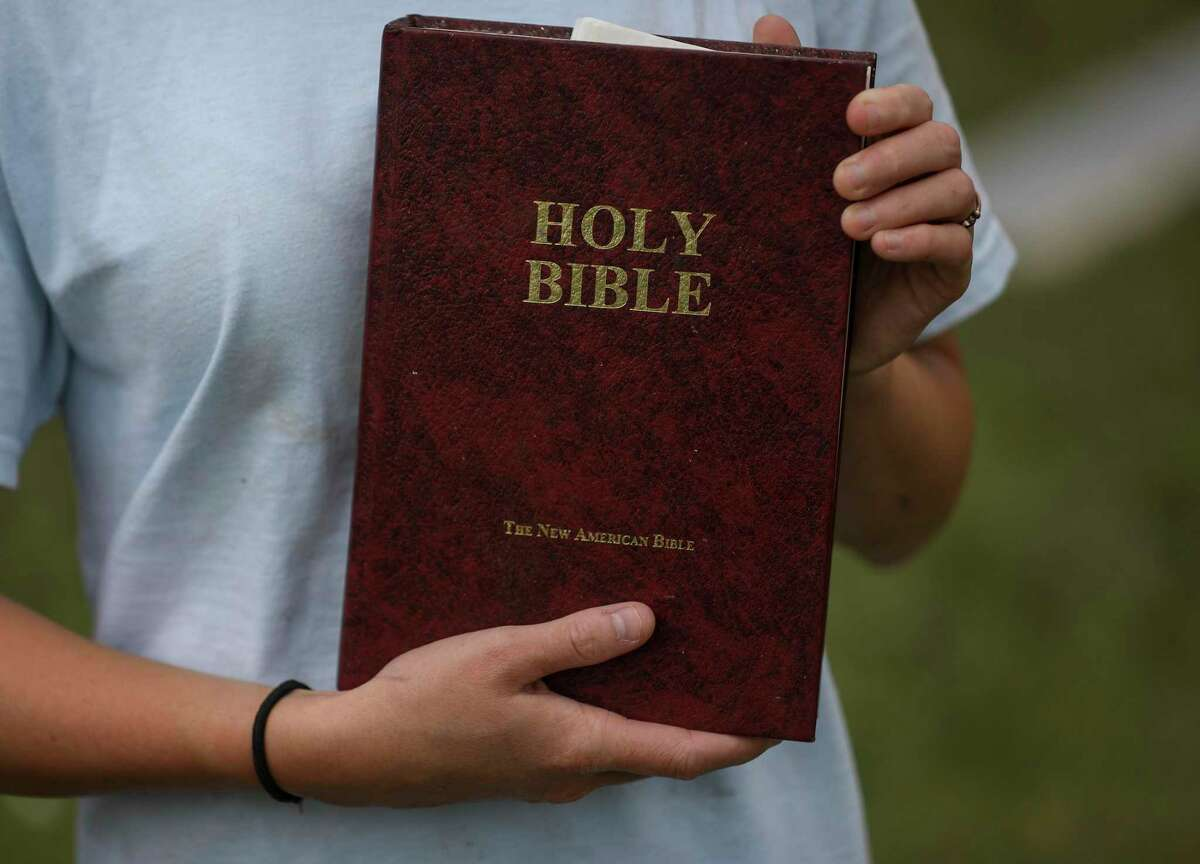 Tyler Ellis, 15, holds a copy of her Bible on Thursday, Aug. 27, 2020, in Holmwood, La. Ellis said that she left the Bible on her bed when she evacuated with her family ahead of Hurricane Laura, which destroyed part of her house and knocked down one of her bedroom walls. She said she found the Bible undisturbed when they returned.