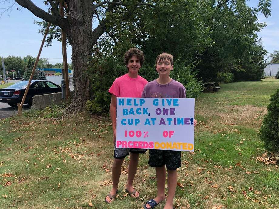 Aleksander Duz, left, and his brother, Julian Duz, right, said  it felt great to participate in a family lemonade stand to raise money for  the Orange Volunteer Fire Department. Photo: Jim Leahy / Contributed Photo