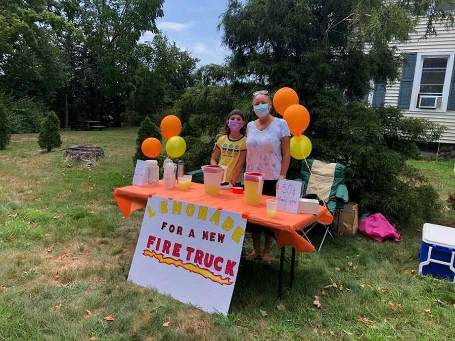 "Kalina Duz, left, and her mother, Aneda Kratzer-Duz, at the lemonade stand they are operating to raise money toward the Orange Volunteer Fire Department's ""Fire Truck 50K Challenge."" Photo: Jim Leahy / Contributed Photo"