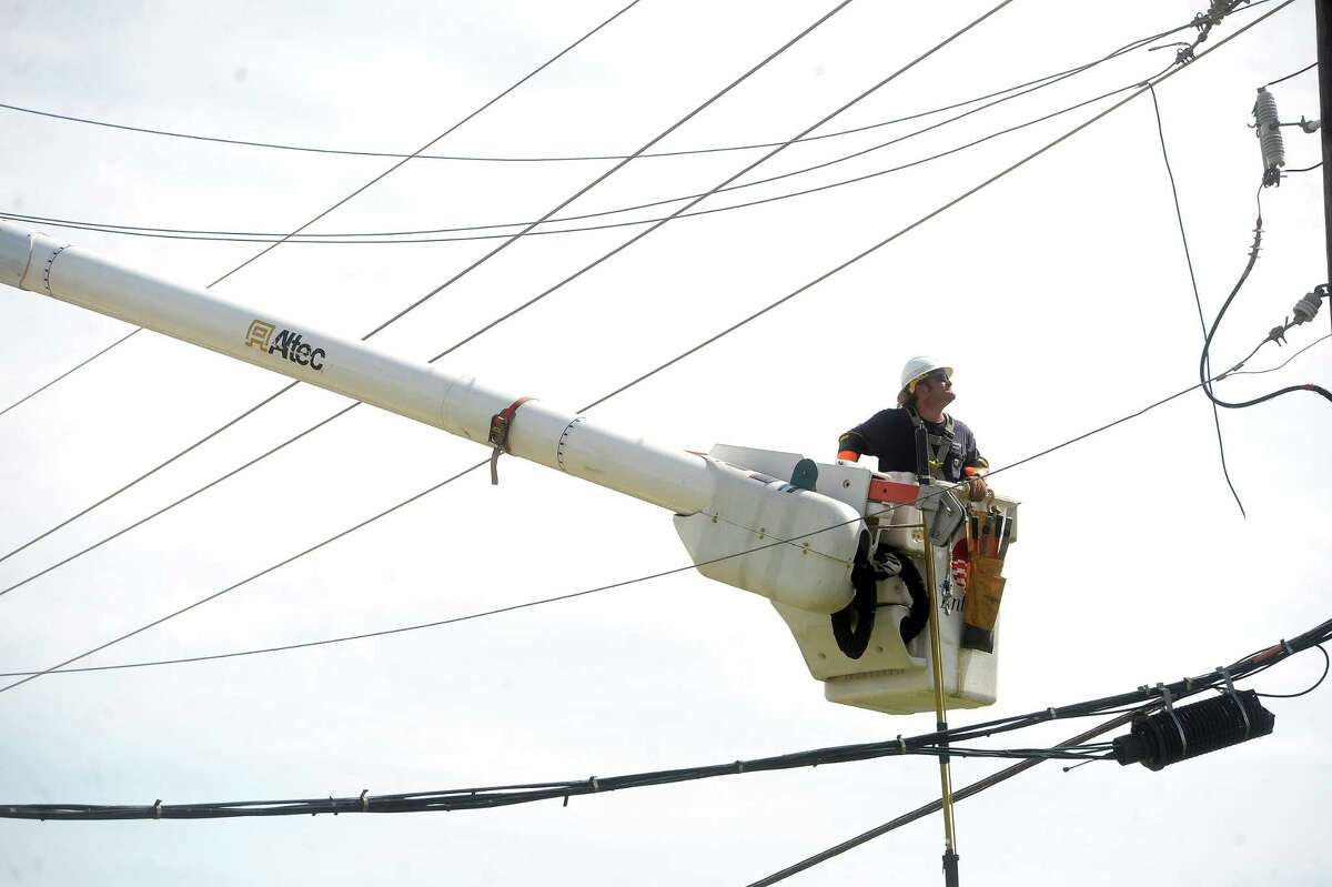 An Entergy worker is hoisted up to work on power lines over FM 365 in Port Arthur Thursday as clean-up and repairs get underway following Hurricane Laura's advance through the region early in the morning. Photo taken Thursday, August 27, 2020 Kim Brent/The Enterprise