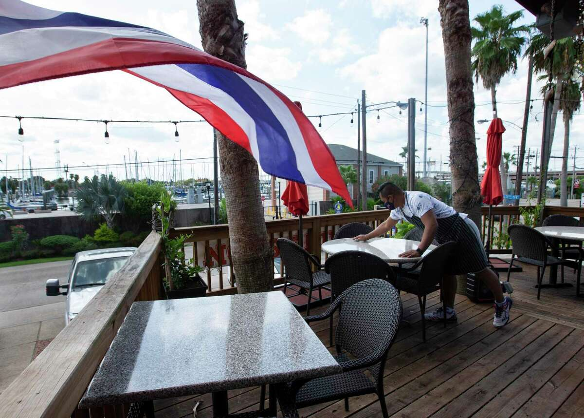 Nam Thai Restaurant & Bar Owner Skyy Rivera cleans tables at the restaurant's patio Thursday, Aug. 27, 2020, in Kemah. The restaurant closed on Wednesday as the area was evacuated, and reopened after Hurricane Laura made landfall near Cameron, Louisiana.