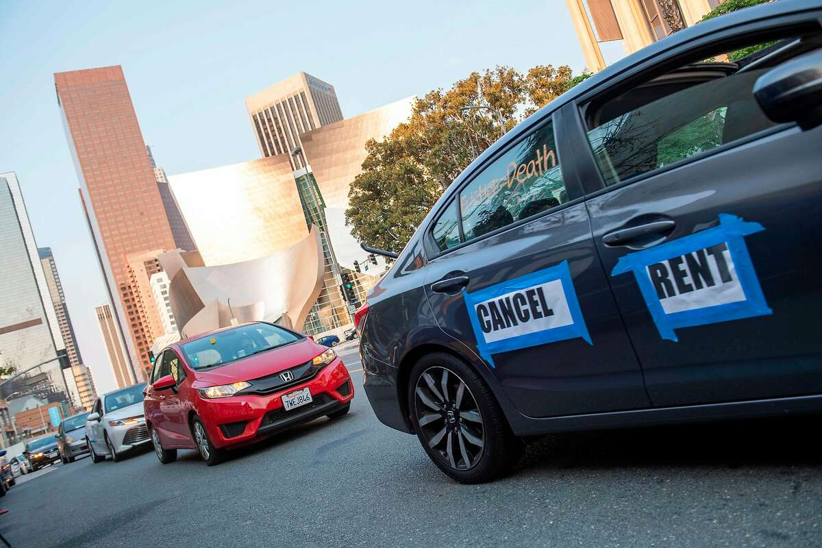 Cars with sign 'Cancel Rent' are seen driving around downtown LA during a protest to cancel rent and avoid evictions amid Coronavirus pandemic on August 21, 2020, in Los Angeles, California. (Photo by VALERIE MACON / AFP) (Photo by VALERIE MACON/AFP via Getty Images)