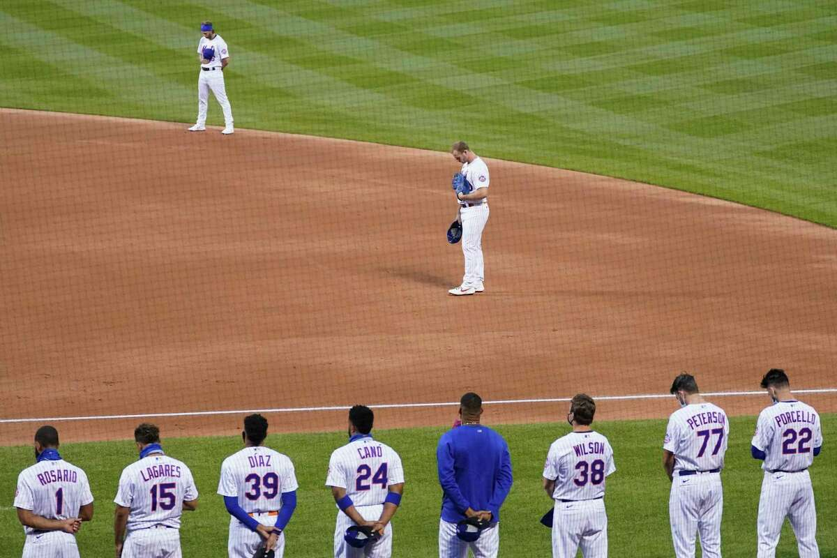 The New York Mets and the Miami Marlins stand on the field and bow their heads at the start of their baseball game before walking off in protest, Thursday, Aug. 27, 2020, in New York. The teams jointly walked off the field after a moment of silence, draping a Black Lives Matter T-shirt across home plate as they chose not to start their scheduled game Thursday night. (AP Photo/John Minchillo)