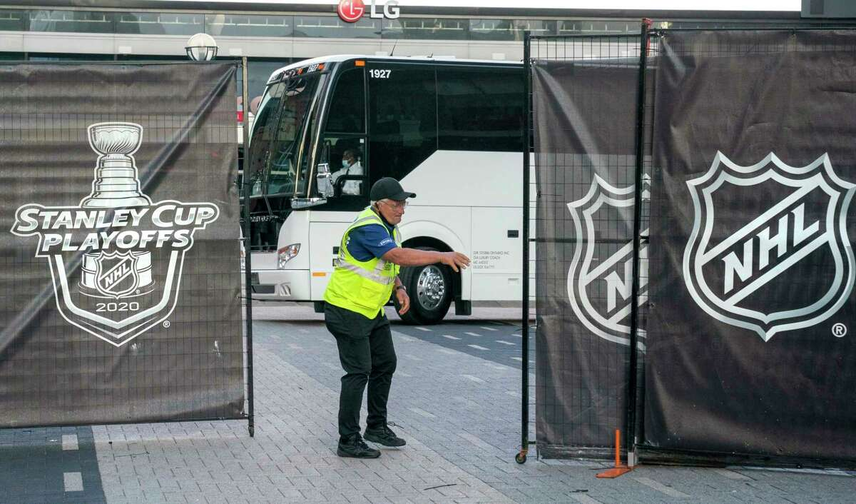 A security guard opens a gate for an empty player bus as it departs Scotiabank Arena in Toronto on Thursday, Aug. 27, 2020. The NHL postponed two days of playoff games Thursday after withering criticism from Black players who said the league was slow to acknowledge the police shooting of Jacob Blake in Wisconsin. (Frank Gunn/The Canadian Press via AP)