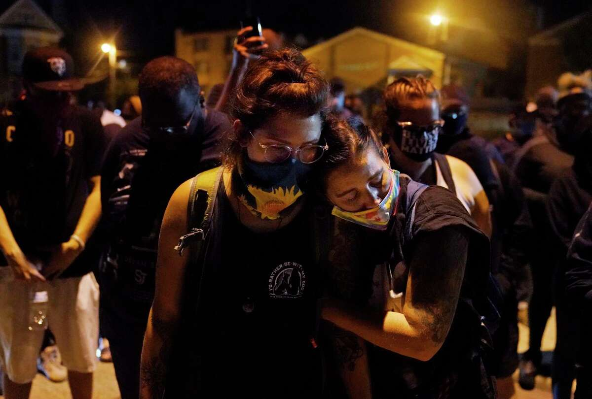 Protesters observe a moment of silence while marching Wednesday night, Aug. 26, 2020, in Kenosha, Wis., near the scene of a fatal shooting Tuesday night. A white, 17-year-old police admirer was arrested Wednesday after two people were shot to death Tuesday during a third straight night of protests in Kenosha over the police shooting of a Black man, Jacob Blake. (AP Photo/David Goldman)