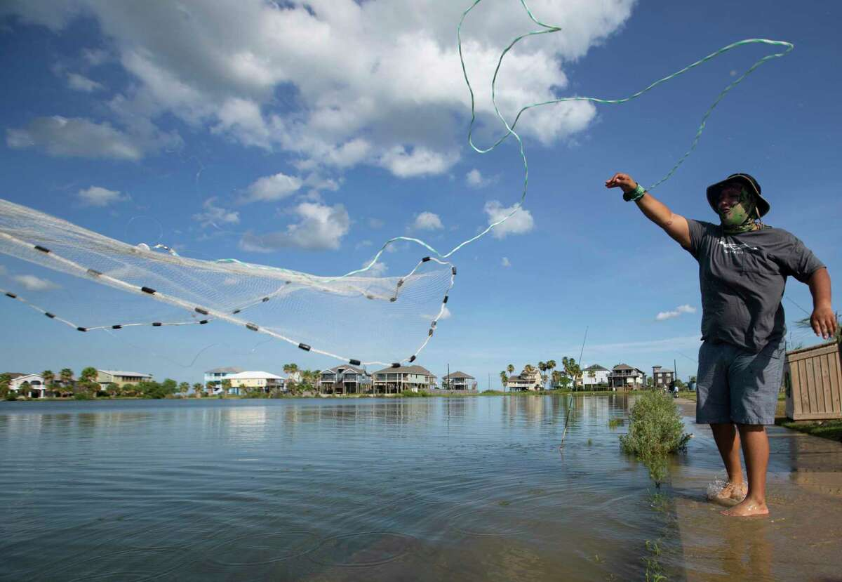 Roberto Del Angel casts a net while fishing with family Thursday, Aug. 27, 2020, in Seabrook. Hurricane Laura made landfall near Cameron, Louisiana, early Thursday morning and did not impact the Houston area. Many people take advantage of the nice weather to go fishing along the Galveston Bay area.
