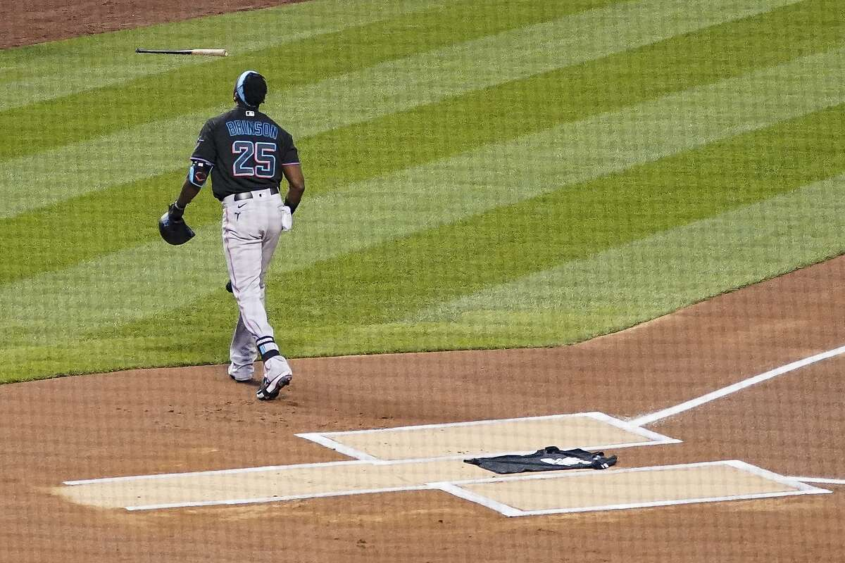 Miami Marlins center fielder Lewis Brinson (25) walks away from home plate after placing a Black Lives Matter shirt on home plate as teammates and the New York Mets walk off the field at the start of their baseball game, Thursday, Aug. 27, 2020, in New York. The teams jointly walked off the field after a moment of silence, draping the shirt across the plate as they chose not to start their scheduled game Thursday night. (AP Photo/John Minchillo)