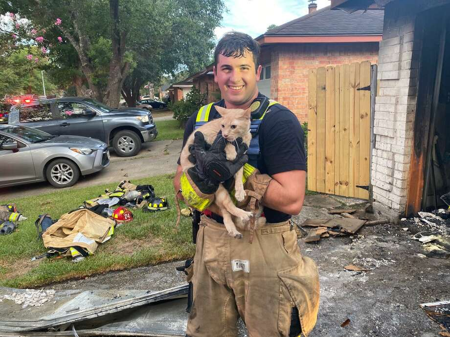 Spring Firefighter Charles Becker holds the cat he saved from the smoky interior of a house after the Spring Fire Department extinguished a garage fire in the Greengate Place subdivision on Aug. 27, 2020. Photo: Courtesy Of The Spring Fire Department / Submitted