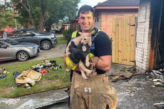 Spring Firefighter Charles Becker holds the cat he saved from the smoky interior of a house after the Spring Fire Department extinguished a garage fire in the Greengate Place subdivision on Aug. 27, 2020.