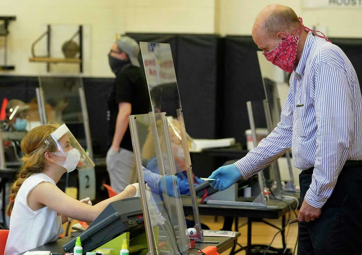 Allison Aungier, an election clerk, left, works behind a plastic barrier at her desk wearing a face mask, face shield and gloves as she checks in voters at the Metropolitan Multi-Service Center, 1475 West Gray, Friday, July 10, 2020, in Houston.