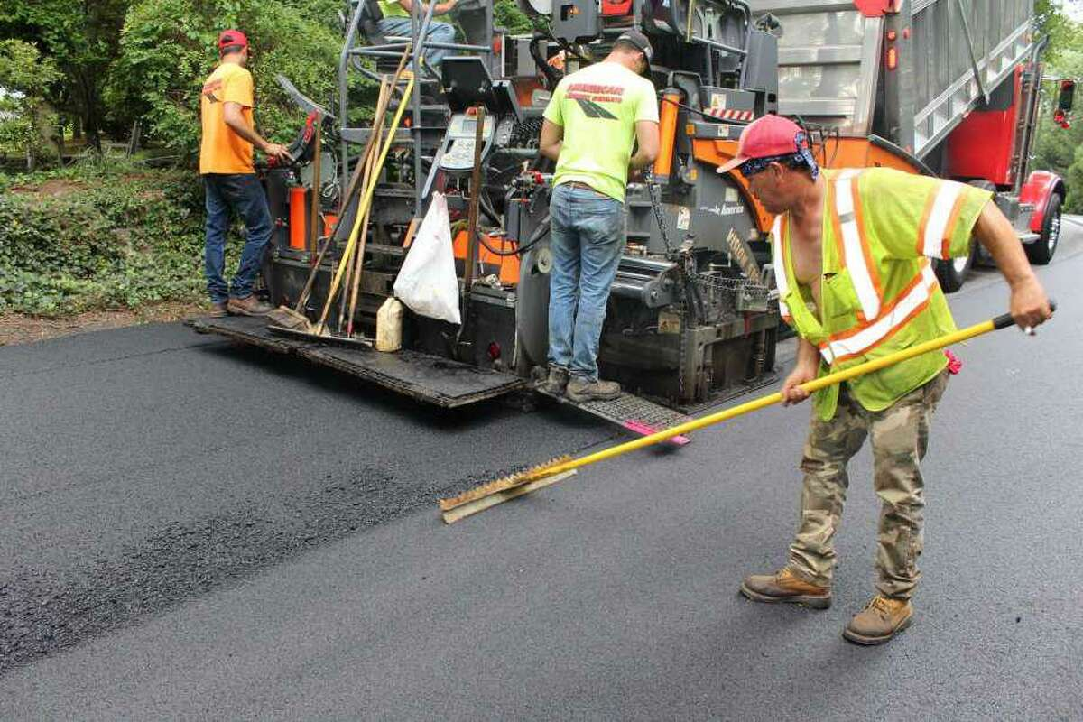 Workers lay down fresh layer of asphalt.