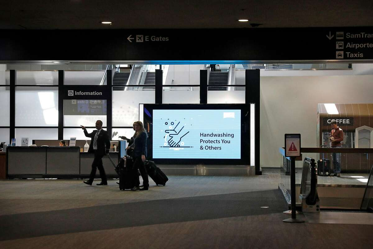 Hand washing and social distancing signs serve as reminders for travelers, staff and flight crew at San Francisco International Airport during the coronavirus pandemic on Wednesday, April 1, 2020.
