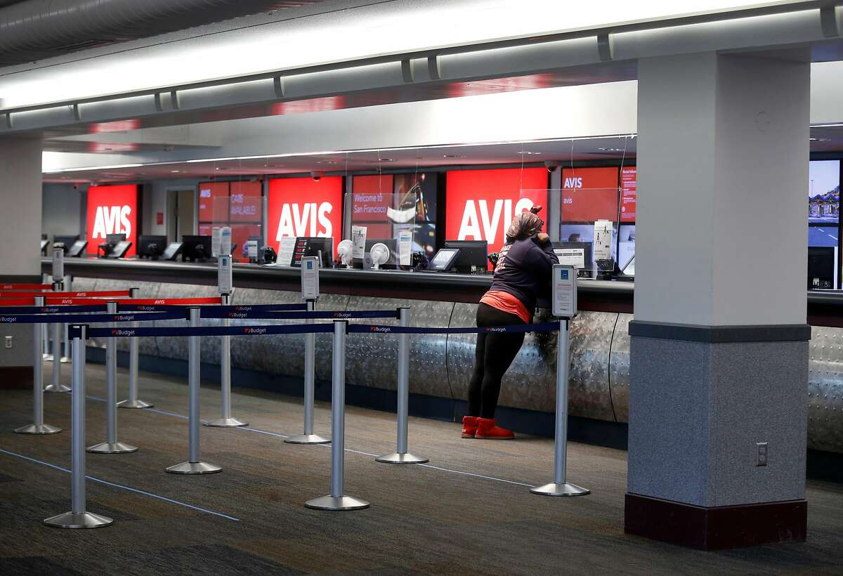 A traveler checks-in at a counter in the Rental Car Center, which is practically deserted at SFO in San Francisco, Calif. on Wednesday, May 6, 2020. Car rental companies are taking a huge hit financially while the coronavirus pandemic continues to cripple the travel industry.
