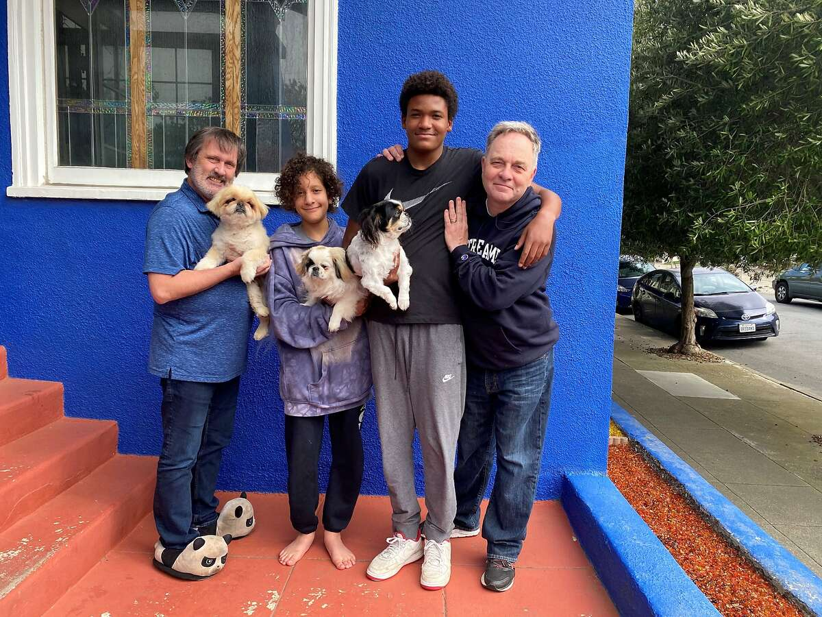 The Fisher-Paulson family pose with their dogs Buddyboy, Bandit and Queenie.