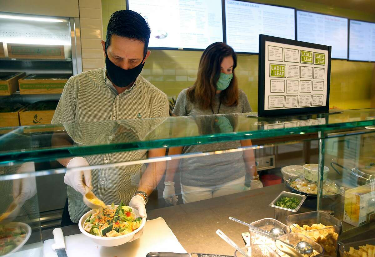 Steve Sarver prepares a salad with business partner Jennifer Sarver at their Ladle and Leaf cafe and restaurant in the Crocker Galleria mall in San Francisco, Calif. on Tuesday, Aug. 25, 2020. Some businesses have remained open despite few office workers and commuters populating the Financial District during the coronavirus shutdown.