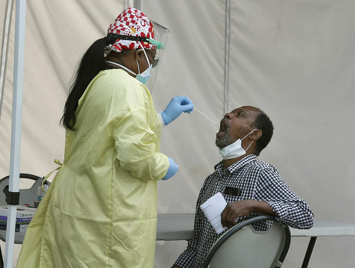A healthcare worker collects an oral sample from a resident at a walk-up COVID-19 testing site at the Roots Community Health Center in Oakland, Calif. on Wednesday, Aug. 26, 2020.