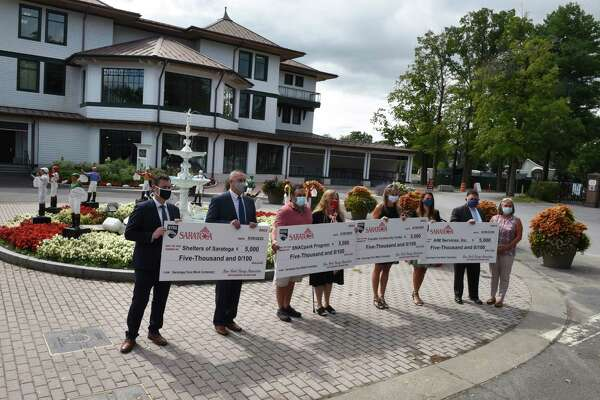 Saratoga charity recipients holds symbolic $5,000 checks totaling $20,00 presented to them by the New York Racing Association on Friday, Aug. 28, 2020, at Saratoga Race Course in Saratoga Springs, N.Y. Campaign beneficiaries awarded by NYRA include; AIM Services, Inc.; Franklin Community Center; Shelters of Saratoga and the SNACpack Program (Saratoga Nutrition Assistance for Children). Checks were presented Mayor Meg Kelly and Dave O'Rourke, president and CEO, NYRA. (Will Waldron/Times Union)
