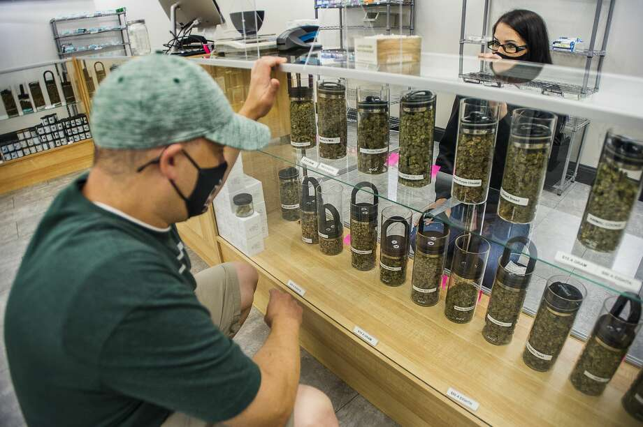 Bobbi Warren, Manager of Nature's Medicines Dispensary, right, assists customer Ryan Rogers, left, as he selects a marijuana strain to purchase Friday, Aug. 28, 2020 inside the business at 3480 E. North Union Rd. in Bay City. (Katy Kildee/kkildee@mdn.net) Photo: (Katy Kildee/kkildee@mdn.net)