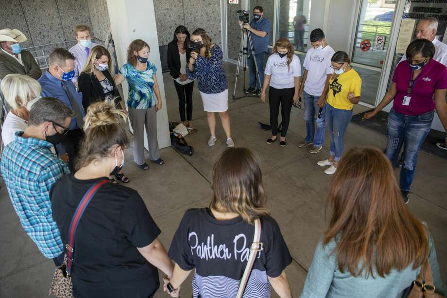 The families of Leilah Hernandez and Joseph Griffith, who were victims during a mass shooting, gather to announce the filing of a lawsuit against the man who sold the gun to the shooter and the gun manufacturer on Friday, Aug. 28, 2020 at the Ector County Courthouse. Connection Christian Church co-pastor Dawn Weaks leads those who gathered in prayer. Jacy Lewis/Reporter-Telegram Photo: Jacy Lewis/Reporter-Telegram / MRT